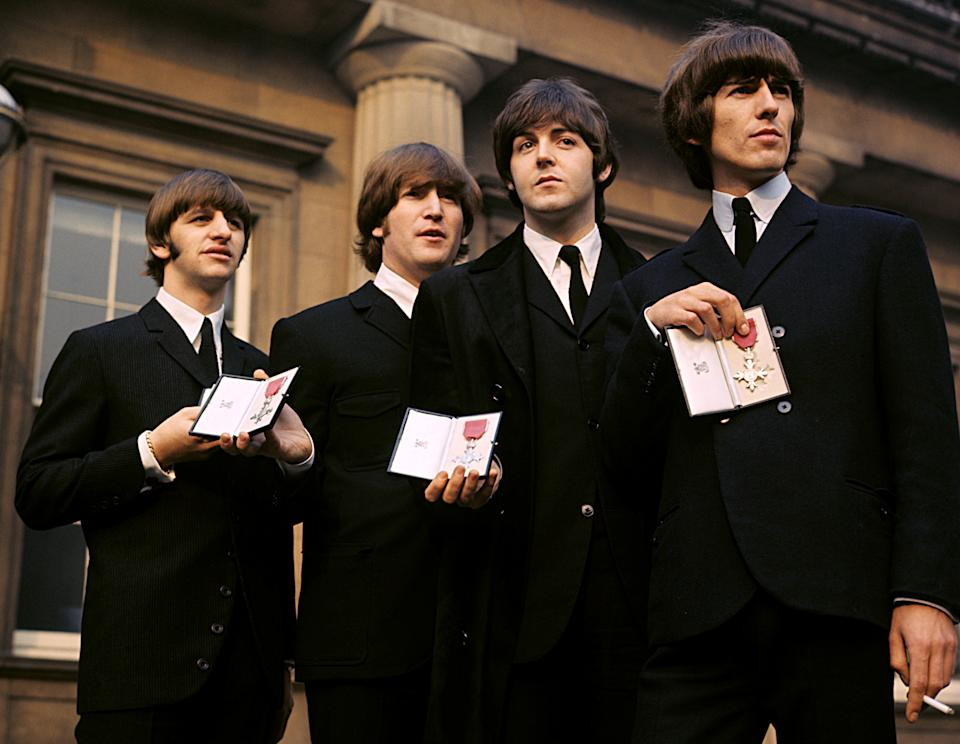 The Beatles showing their MBE Insignias in the forecourt after receiving them from the Queen. (l-r) Ringo Starr, John Lennon, Paul McCartney and George Harrison.