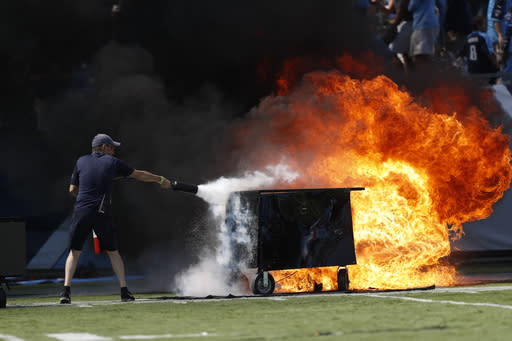 A fire from a pyrotechnics machine is extinguished before an NFL football game between the Tennessee Titans and the Indianapolis Colts Sunday, Sept. 15, 2019, in Nashville, Tenn. (AP Photo/Wade Payne)