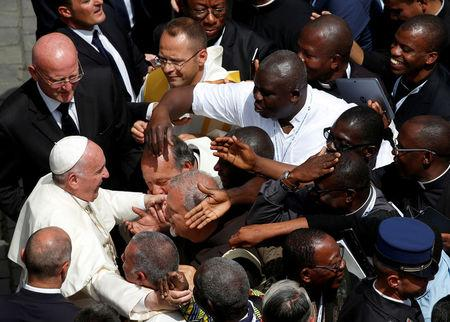 FILE PHOTO : Pope Francis (L) is greeted by priests at the end of a mass for the Jubilee of Priests at St. Peter's Square at the Vatican June 3, 2016. REUTERS/Alessandro Bianchi/File Photo