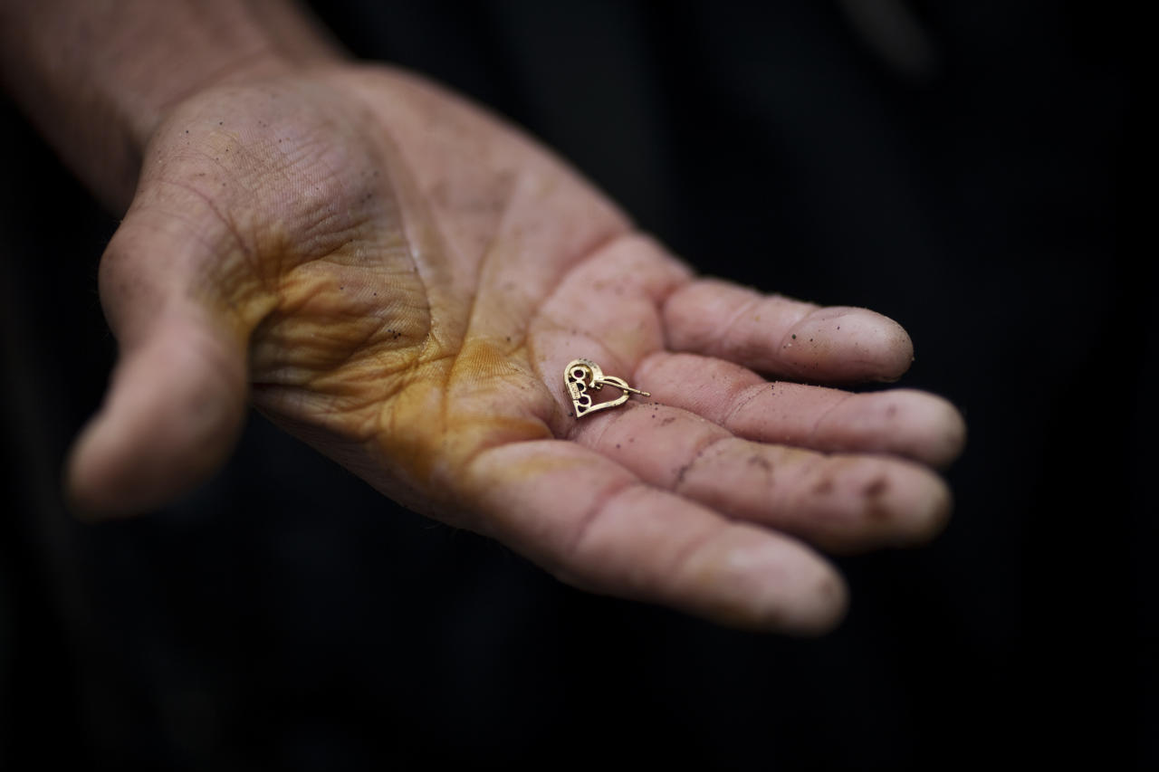 """In this photo taken Wednesday Oct. 19, 2011, a man holds up a gold ring he found while searching for scrap metal in contaminated water at the bottom of one of the biggest trash dumps in the city, known as """"The Mine,"""" in Guatemala City. Hundreds of informal workers descend daily into the mounds of the landfill and the rushing waters that come from a storm tunnel and a sewer at the bottom of a gorge to search for scrap metal to sell. This activity known locally as """"mining"""" is extremely dangerous due to mud slides and collapses, but earns many of them about 150 quetzals ($20 dollars) a day, nearly twice the minimum daily wage. AP Photo/Rodrigo Abd)"""