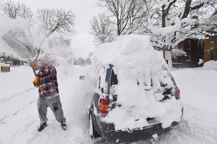 <p>Kevin Deiner of Erie, Pa., digs out his Ford Escape buried on West Sixth Street Saturday, Dec. 30, 2017. ( Photo: Jack Hanrahan/Erie Times-News via AP) </p>