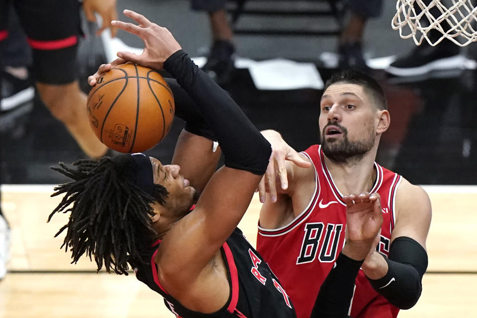 Toronto Raptors forward Freddie Gillespie, left, grabs a rebound next to Chicago Bulls center Nikola Vucevic during the second half of an NBA basketball game in Chicago, Thursday, May 13, 2021. The Bulls won 114-102. (AP Photo/Nam Y. Huh)