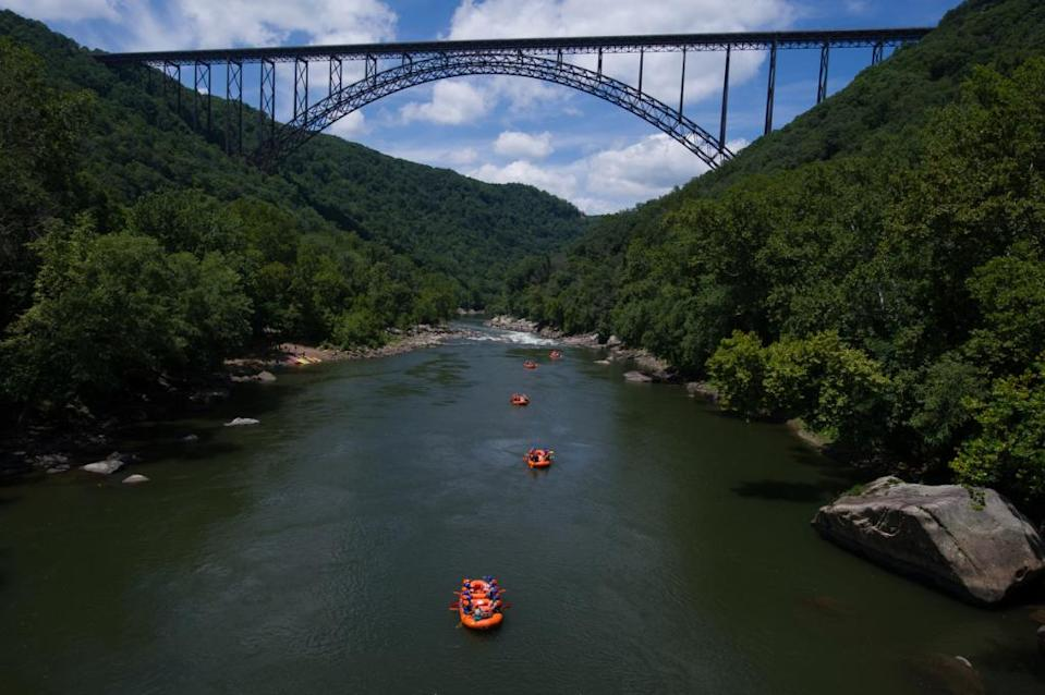 FAYETTVILLE,WV-JULY25: A group of paddlers from Adventures on the Gorge approach the New River Gorge Bridge on their way to the last set of rapids for the day on the New River.