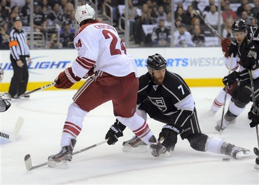 Los Angeles Kings defenseman Rob Scuderi, right, kicks the puck away from Phoenix Coyotes center Kyle Chipchura during the first period of Game 3 of the NHL hockey Stanley Cup Western Conference finals, Thursday, May 17, 2012, in Los Angeles. (AP Photo/Mark J. Terrill)