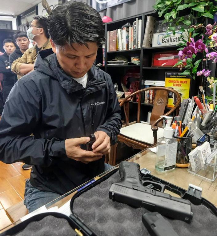 Brian Xia, 44, picks up the gun he ordered at a gun shop in Arcadia, California, on March 15. Gun sales are soaring across the country as buyers seek protection during the coronavirus pandemic.