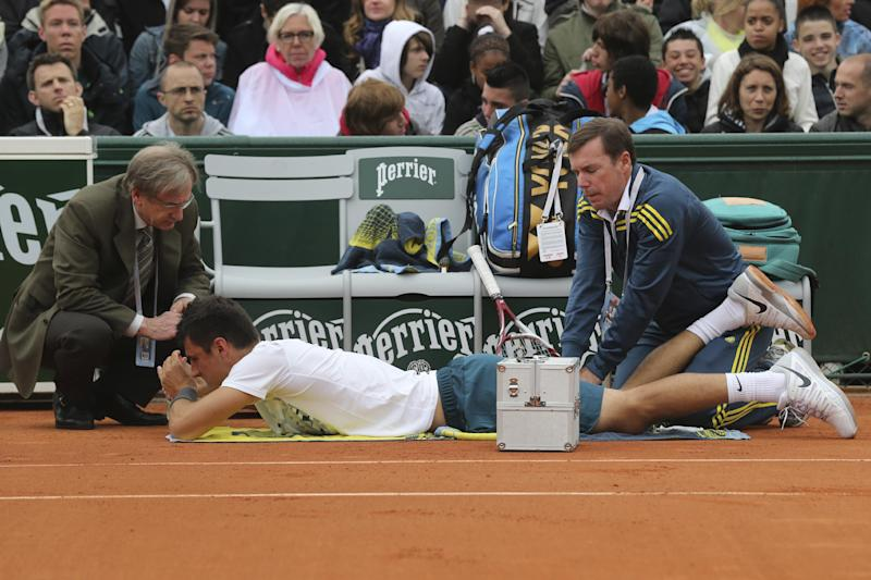 Australia's Bernard Tomic is treated for an injury in his first round match against Romania's Victor Hanescu at the French Open tennis tournament, at Roland Garros stadium in Paris, Tuesday, May 28, 2013. Tomic retired later in the match. (AP Photo/Michel Euler)