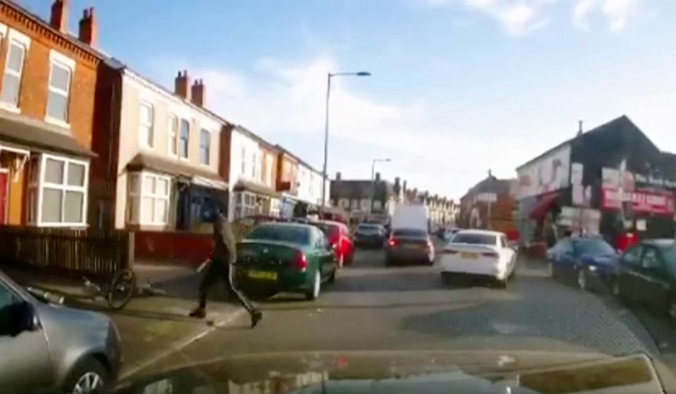 Disturbing dash-cam footage shows the moment a cyclist appears to stab a car passenger with a giant blade during a shocking broad daylight knife attack. (SWNS)