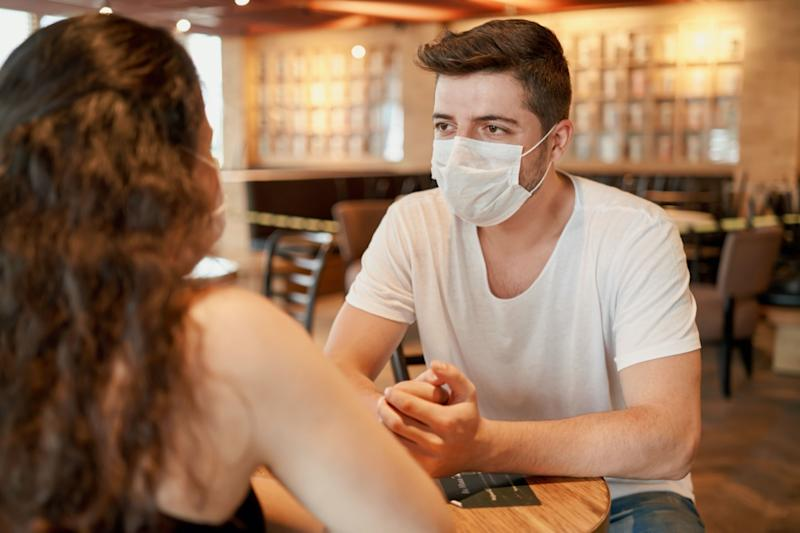 Two people wearing surgeon masks is sitting in a cafe and chatting