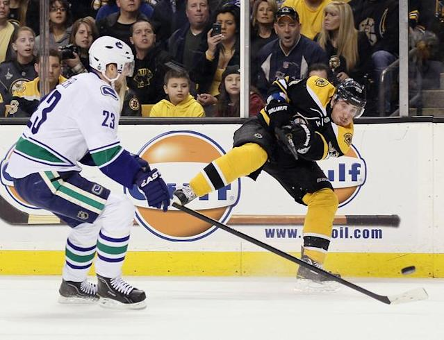 BOSTON, MA - JANUARY 07: Brad Marchand #63 of the Boston Bruins takes a shot as Alexander Edler #23 of the Vancouver Canucks defends on January 7, 2012 at TD Garden in Boston, Massachusetts. (Photo by Elsa/Getty Images)