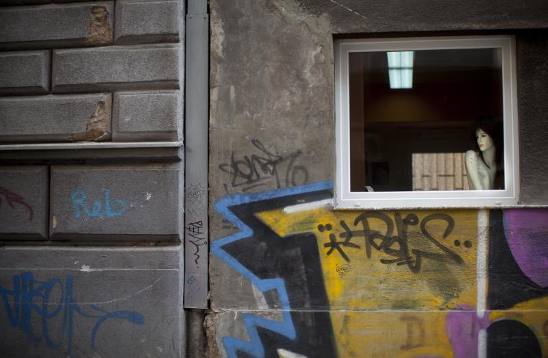 A mannequin is placed next to a window of a building marked with graffiti in the center of Sarajevo, Bosnia, Thursday, April 5, 2012. Sarajevo marks the 20th anniversary of the start of the 44-month Bosnian Serb siege of Sarajevo, part of the 1991-95 Bosnian war. (AP Photo/Anja Niedringhaus)