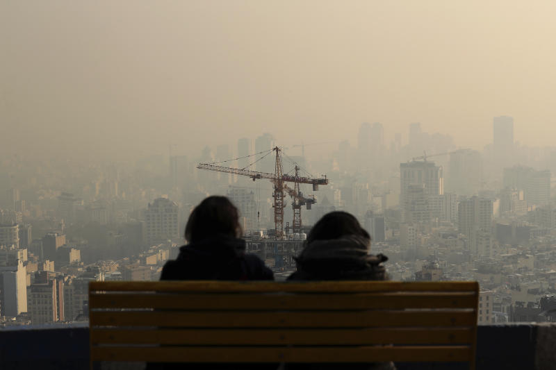 People look at the skyline through polluted air, in the Velenjak mountainous area of Tehran, Iran Monday, Dec. 23, 2019. Dangerously poor air quality forced Iran's government on Monday to keep all schools closed in the capital, Tehran, and other cities. Schools were closed since Saturday, and will remain closed until Wednesday, the end of the week in Iran, according to the official IRNA news agency. Tehran's air is among the most polluted in the world. (AP Photo/Ebrahim Noroozi)