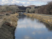 Water flows through an irrigation canal in Fernley, Nev. in this photo taken Thursday, March 18, 2021. The town founded a century ago by pioneers lured to the West with the promise of free land and cheap water is suing the U.S. government over plans to renovate the earthen canal that burst and flooded nearly 600 homes in Fernley in 2008. (AP Photo/Scott Sonner)