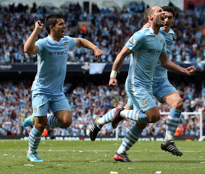 Manchester City's Pablo Zabaleta, center, celebrates scoring against Queens Park Rangers with teammates Gareth Barry, right, and Sergio Aguero during their English Premier League soccer match at the Etihad Stadium, Manchester, England, Sunday May 13, 2012. (AP Photo/Jon Super)
