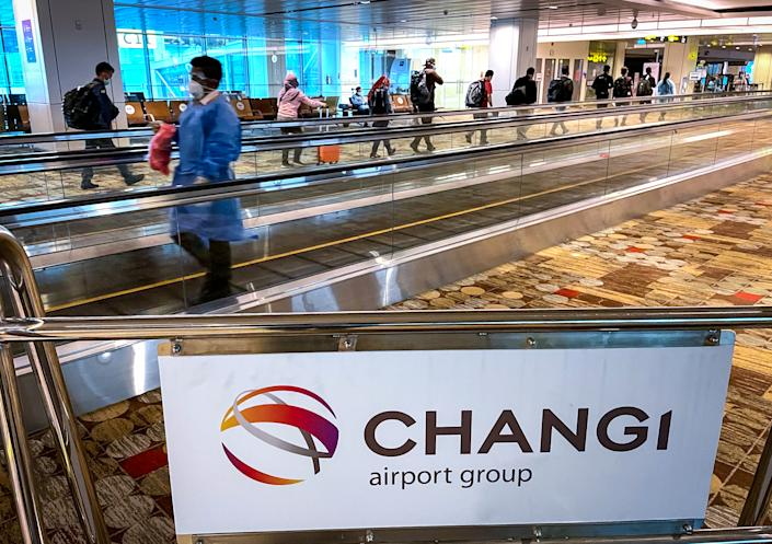 SINGAPORE, SINGAPORE - JULY 14: A member of staff wearing protective clothign and a face mask walks in front of passengers walking in a single line towards their boarding gate at Changi International Airport on July 14, 2021 in Singapore, Singapore. Singapore's Changi Airport, one of the world's key transit hubs, has seen passenger numbers plummet as the ongoing Covid-19 pandemic continues to have a severe impact on air travel. (Photo by David Gray/Getty Images)