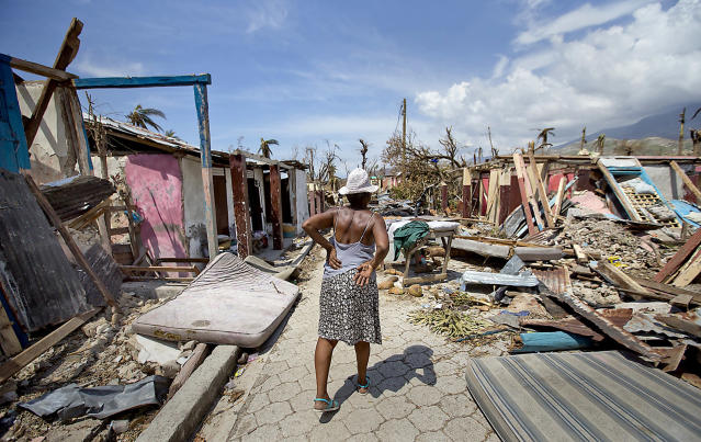 <p>An elderly woman walks along a debris filled street in Roche a Bateau, Haiti on Sunday, Oct. 9, 2016. (Photo: Patrick Farrell/Miami Herald/TNS via Getty Images) </p>
