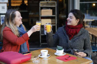 Women enjoy a cafe and an orange juice at a café terrace Wednesday, May, 19, 2021 in Strasbourg, eastern France. It's a grand day for the French. Café and restaurant terraces are reopening Wednesday after a shutdown of more than six months deprived people of what feels like the essence of life — sipping coffee and wine with friends outdoors — to save lives during the coronavirus pandemic. (AP Photo/Jean-Francois Badias)