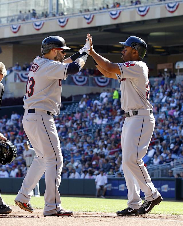 Cleveland Indians' Michael Bourn, right, welcomes Nick Swisher, left, at home plate after they both scored on Swisher's 2 RBI home run off Minnesota Twins starting pitcher Scott Diamond (58) during the first inning of an MLB American League baseball game in Minneapolis, Sunday, Sept. 29, 2013. (AP Photo/Ann Heisenfelt)