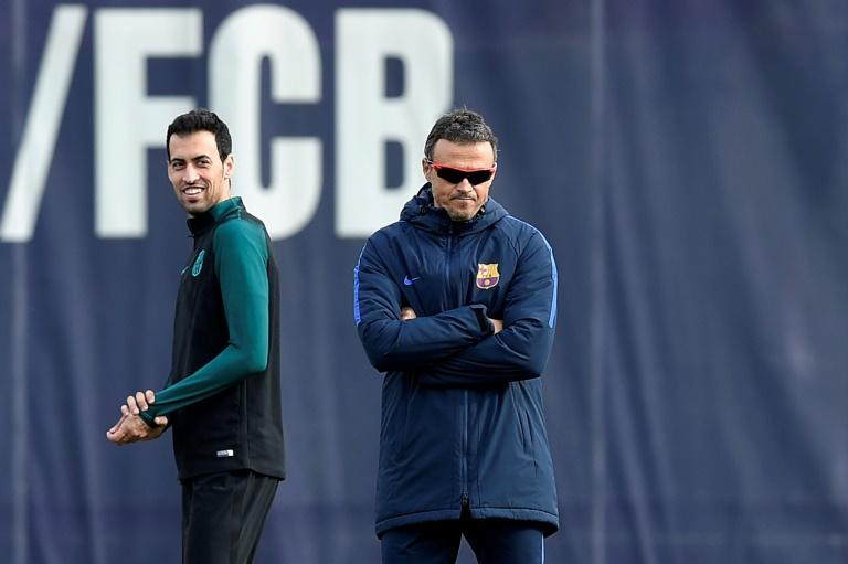 Barcelona's Sergio Busquets smiles past Barcelona's coach Luis Enrique during a training session