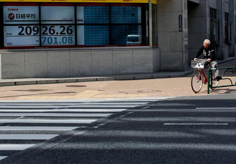 FILE PHOTO: A man in a bicycle stops in front of an electronic board showing the Nikkei stock index outside a brokerage in Tokyo, Japan, March 25, 2019. REUTERS/Kim Kyung-hoon