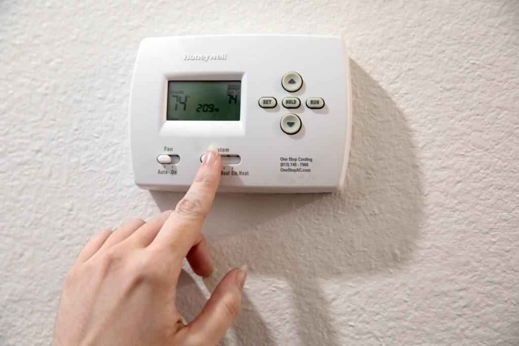 A person turns down the heat in their home.
