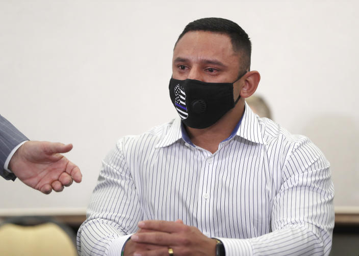 Houston Police officer Felipe Gallegos tears up as Rusty Hardin speaks during a press conference at Hilton Americas, Tuesday, Jan. 26, 2021, in Houston. Gallegos has been charged with murder and is among additional officers who have been indicted as part of an ongoing investigation into a Houston Police Department narcotics unit following a deadly 2019 drug raid, prosecutors announced Monday. (Karen Warren/Houston Chronicle via AP)