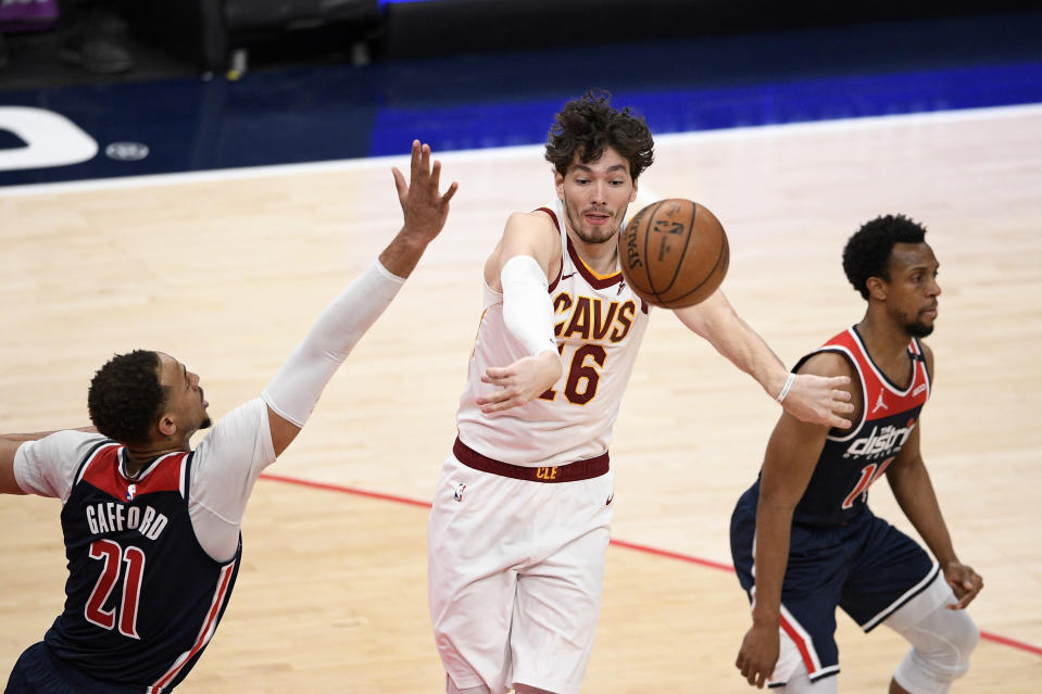 Cleveland Cavaliers forward Cedi Osman (16) passes the ball between Washington Wizards center Daniel Gafford (21) and guard Ish Smith, right, during the second half of an NBA basketball game Friday, May 14, 2021, in Washington. (AP Photo/Nick Wass)