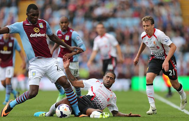 Liverpool's Glen Johnson (centre) slides in on Aston Villa's Christian Benteke (left) as Leiva Lucas (right) looks on