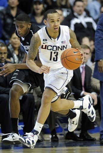 Connecticut's Shabazz Napier, right, is pursued by Providence's Kris Dunn during the second half of Connecticut's 63-59 overtime win in an NCAA college basketball game in Storrs, Conn., Saturday, March 9, 2013. (AP Photo/Fred Beckham)