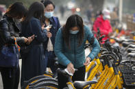 A woman wearing a face mask to help curb the spread of the coronavirus uses an alcohol tissue to disinfect a bicycle of bike-sharing companies during the morning rush hour in Beijing, Monday, Oct. 26, 2020. Schools and kindergartens have been suspended and communities are on lockdown in Kashgar, a city in China's northwest Xinjiang region, after more than 130 asymptomatic cases of the coronavirus were discovered. (AP Photo/Andy Wong)
