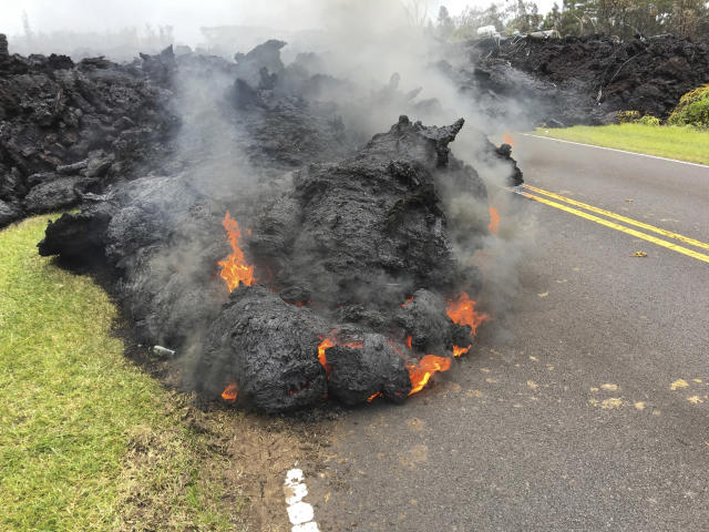 <p>Lava from the Kilauea volcano moves across the road in the Leilani Estates in Pahoa, Hawaii, Saturday, May 5, 2018. Hundreds of anxious residents on the Big Island of Hawaii hunkered down Saturday for what could be weeks or months of upheaval as the dangers from an erupting Kilauea volcano continued to grow. (Photo: Marco Garcia/AP) </p>