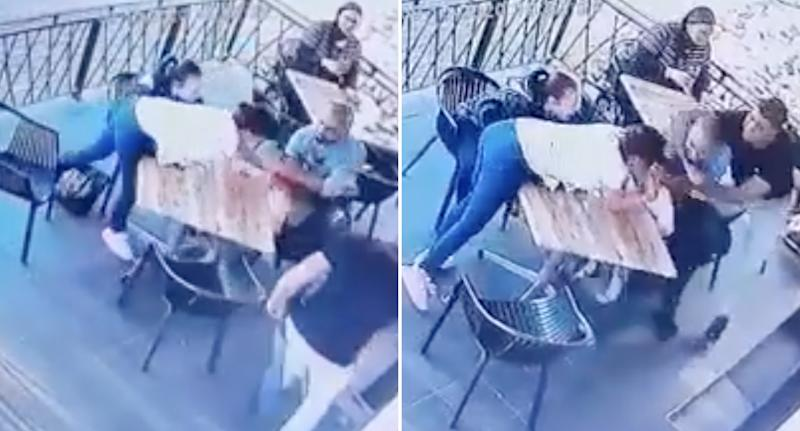 A man runs to a restaurant table and grabs a little girl.  People try to stop him.