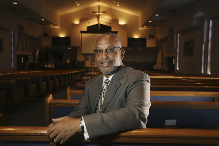 """CORRECTS NAME OF CHURCH TO FIRST INSTITUTIONAL BAPTIST CHURCH FROM INSTITUTIONAL BAPTIST CHURCH In this Tuesday, July 30, 2019 photo, Civil Rights leader Rev. Dr. Warren H. Stewart Sr. sits in the sanctuary of his church, the First Institutional Baptist Church, in Phoenix. Phoenix's past segregation has been in focus after this summer's national outrage over a videotaped encounter of police pointing guns and cursing at a black family. """"That has long been a reality for African Americans, to not be treated fairly by the police,"""" said Stewart. """"Segregation has been outlawed, but the remnants of systemic racism and discrimination remain."""" (AP Photo/Ross D. Franklin)"""