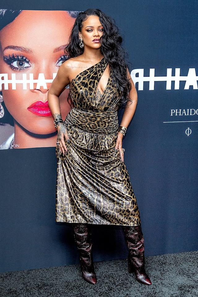 wears a Saint Laurent one-shoulder leopard-print midi dress with a keyhole detail and ruched waistband and croc-embossed boots at the launch of her first visual autobiography, <em>Rihanna,</em> at the Guggenheim Museum in N.Y.C.