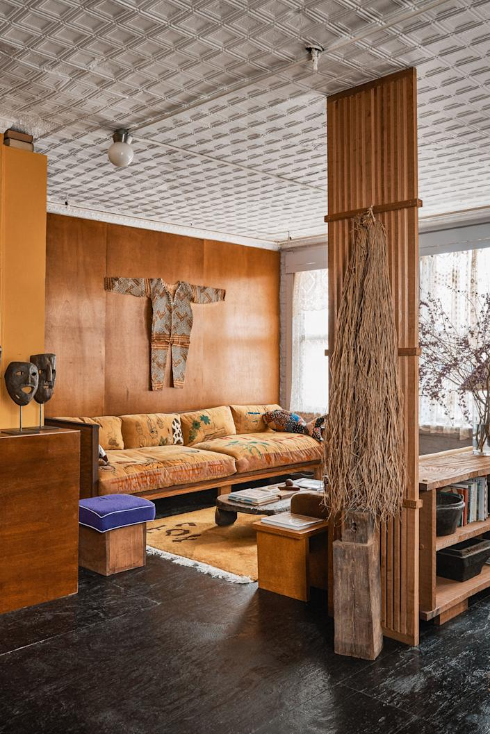 "<div class=""caption""> In the wood-clad living area of Emily Adams Bode and Aaron Aujla's Chinatown, New York, apartment, a 1940s suit from the Congo hangs above a custom corduroy sofa covered in personal drawings. </div>"