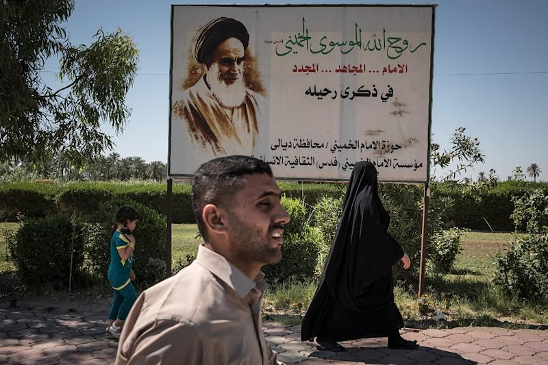 Iraqis walk past a poster of Ayatollah Ruhollah Khomeini, the founder of the Islamic Republic of Iran, in Diyala, Iraq on Sunday, June 4, 2017. (Sergey Ponomarev/The New York Times)