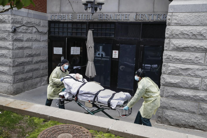 FILE - In this Friday, April 17, 2020 file photo, a patient is wheeled out of the Cobble Hill Health Center nursing home by emergency medical workers in the Brooklyn borough of New York. After 100,000 deaths ravaged the nation's nursing homes and pushed them to the front of the vaccine line, they now face a vexing problem: Skeptical residents and workers balking at getting the shots. (AP Photo/John Minchillo, File)