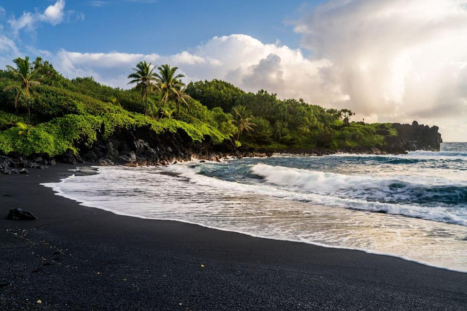"""<p>There's plenty to see at <a href=""""https://hawaiistateparks.org/parks/maui/wai%CA%BBanapanapa-state-park/"""" rel=""""nofollow noopener"""" target=""""_blank"""" data-ylk=""""slk:Wai'anapanapa State Park"""" class=""""link rapid-noclick-resp"""">Wai'anapanapa State Park</a> when camping, but one of the most unique is the beaches the area is known for. This is home to one of Maui's v0lcanic-sand beaches, meaning the sand is black, which is truly special to see. There are also freshwater caves, a natural stone arch, towering palm trees, forests to explore, and wildlife to see. It's hard to go wrong when camping in Hawaii, but this spot is one of the best. </p>"""