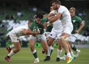 Ireland's Joey Carbery, centre, is tackled by USA's Hanco Germishuys, left and Cam Dolan, right, during the Rugby Union International Summer Series match between Ireland and USA, in Dublin, Ireland, Saturday July 10, 2021. (Donall Farmer/PA via AP)