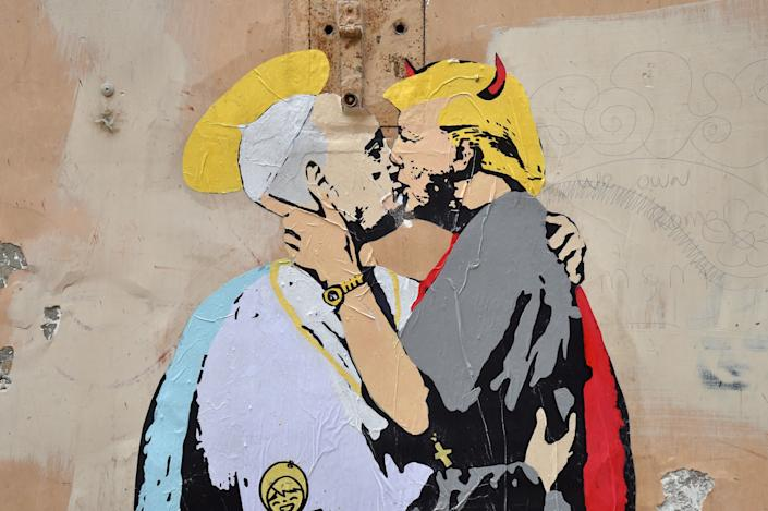 A collage shows Pope Francis kissing US President Donald Trump with a caption by Italian artist TvBoy reading in English and Italian 'The Good forgives the Evil' in tiny letters along Francis belt, on May 11, 2017 near Castel Sant'Angelo in central Rome.
