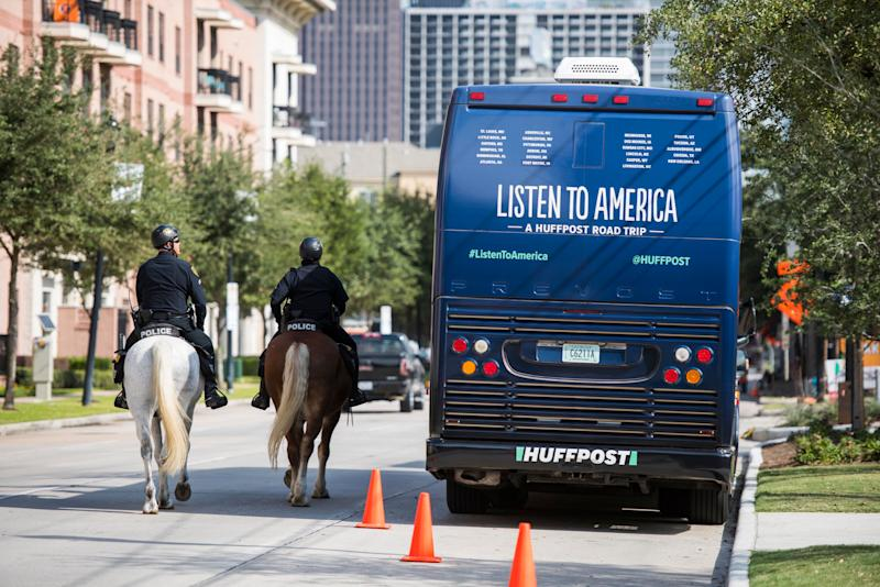 Police officers on horseback make their way around the HuffPost tour bus.
