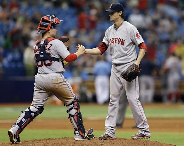 Boston Red Sox starting pitcher Clay Buchholz, right, shakes hands with catcher Christian Vazquez after throwing a complete baseball game shutout over the Tampa Bay Rays, Sunday, Aug. 31, 2014, in St. Petersburg, Fla. The Red Sox won the game 3-0. (AP Photo/Chris O'Meara)