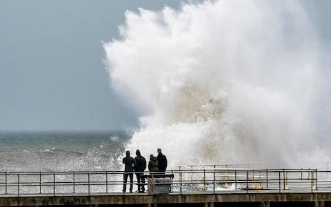 Strong gale force winds, gusting to over 40mph, and the high tide combine to whip huge waves crashing into the sea defences on the promenade in Aberystwyth - Credit: Keith Morris/LNP