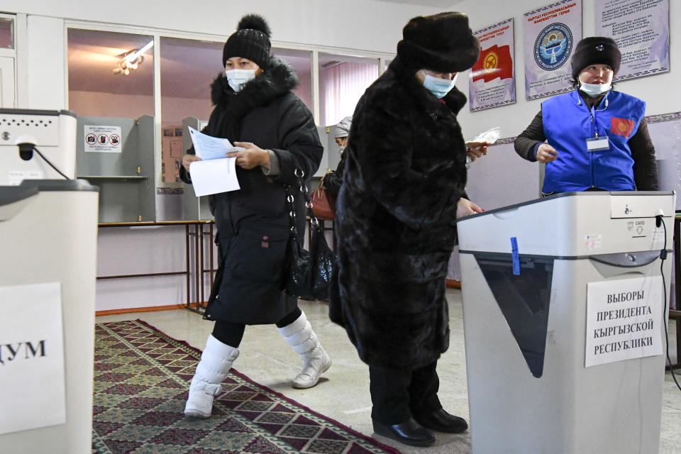 People vote during the presidential elections in Koy-Tash village, about 16 kilometers (10 miles) south of Bishkek, Kyrgyzstan, Sunday, Jan. 10, 2021. Voters in Kyrgyzstan are casting ballots in an early presidential election that follows the ouster of the nation's previous president. President Sooronbai Jeenbekov was forced to step down on Oct. 15 under pressure from demonstrators who challenged the results of a parliamentary vote earlier that month. (AP Photo/Vladimir Voronin)