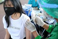A young woman receives the AstraZeneca Covid-19 coronavirus vaccine at a makeshift mass vaccination clinic on Indonesia's resort island of Bali