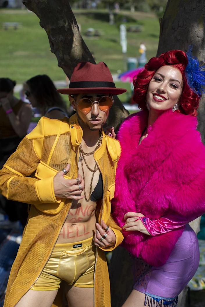 A person in a yellow jacket and boxers and brown cowboy hat, next to a person in purple spandex skirt and pink furry jacket