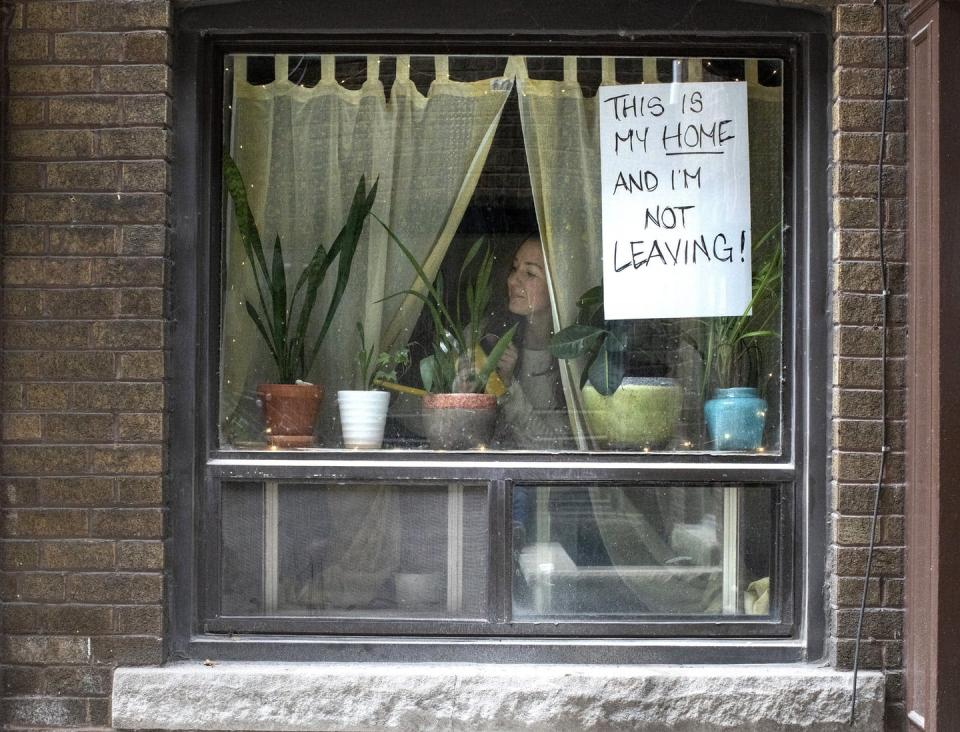 "<span class=""caption"">A woman is pictured at the window of her west Toronto apartment in March 2020 as her landlord issued eviction notices at the start of the pandemic. Secure and affordable housing is a big concern of those collecting social assistance, whether it was CERB or provincial programs.</span> <span class=""attribution""><span class=""source"">THE CANADIAN PRESS/Chris Young</span></span>"