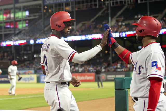 Texas Rangers' Jurickson Profar, front left, is congratulated by Elvis Andrus after scoring on a bases-loaded walk of Shin-Soo Choo by Los Angeles Angels relief pitcher Justin Anderson during the eighth inning of a baseball game Thursday, Aug. 16, 2018, in Arlington, Texas. Texas won 8-6. (AP Photo/Jeffrey McWhorter)