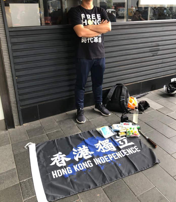 """Man stands next to a flag reading """"Hong Kong Independence"""" as people protest the new security law in Hong Kong"""