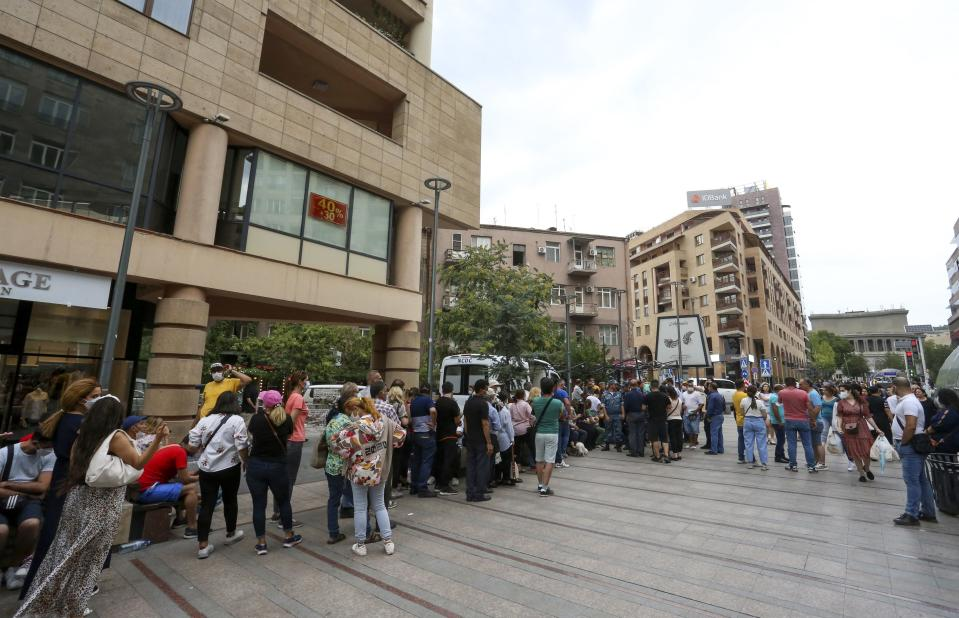 People stand in line for a vaccine shot at a mobile vaccination station in the center of in Yerevan, Armenia, Wednesday, July 14, 2021. Hundreds lined the streets of the Armenian capital to get free coronavirus shots, and some spent night on the streets to save on queueing. Under the Armenian government's directives effective since Friday, foreign nationals can only get AstraZeneca shots at five mobile vaccination points in Yerevan. (Vahram Baghdasaryan/PHOTOLURE via AP)