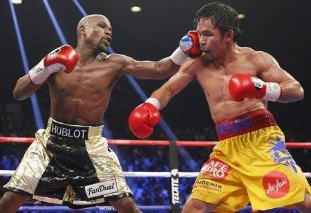 Floyd Mayweather, Jr. of the U.S. lands a left to the face of Manny Pacquiao of the Philippines (R) in the 11th round during their welterweight WBO, WBC and WBA (Super) title fight in Las Vegas, Nevada, May 2, 2015. REUTERS/Steve Marcus